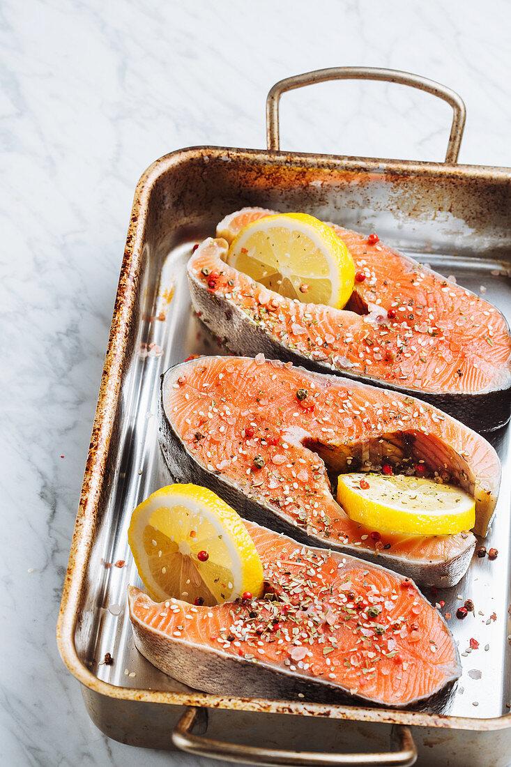 Fresh salmon steaks with aromatic seasoning and lemon slices on metal baking sheet