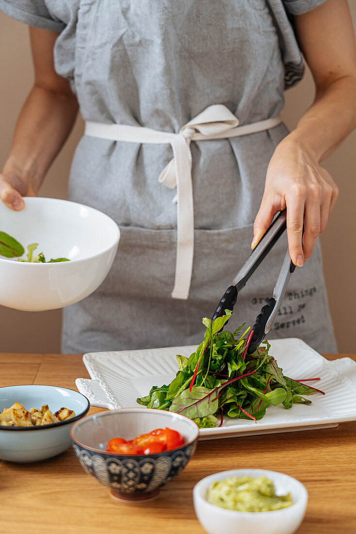 Preparing salad: Fresh green leaves on white plate and ingredients