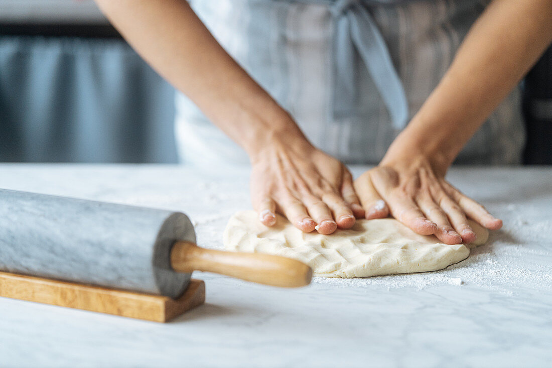 Kneading dough with fingers on marble table with rolling pin