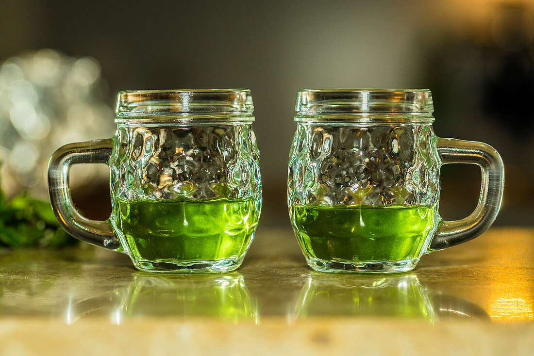 Green absinthe in glasses with handles