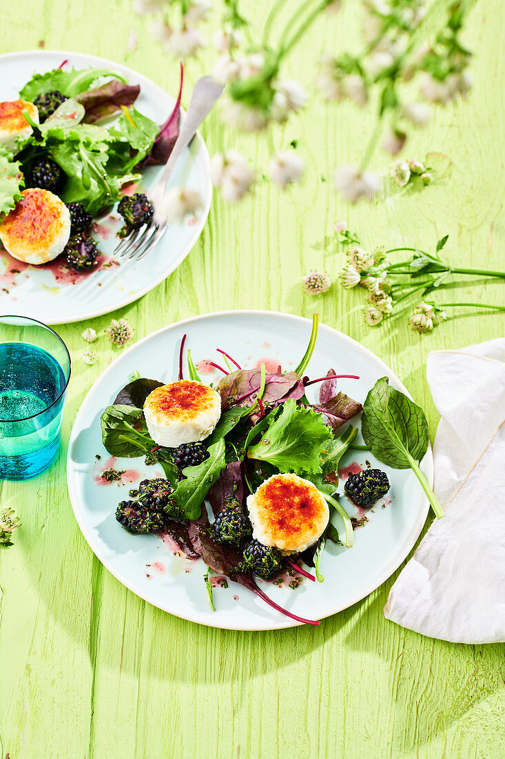 Caramelised goat's cheese rounds on a bed of lettuce with blackberries