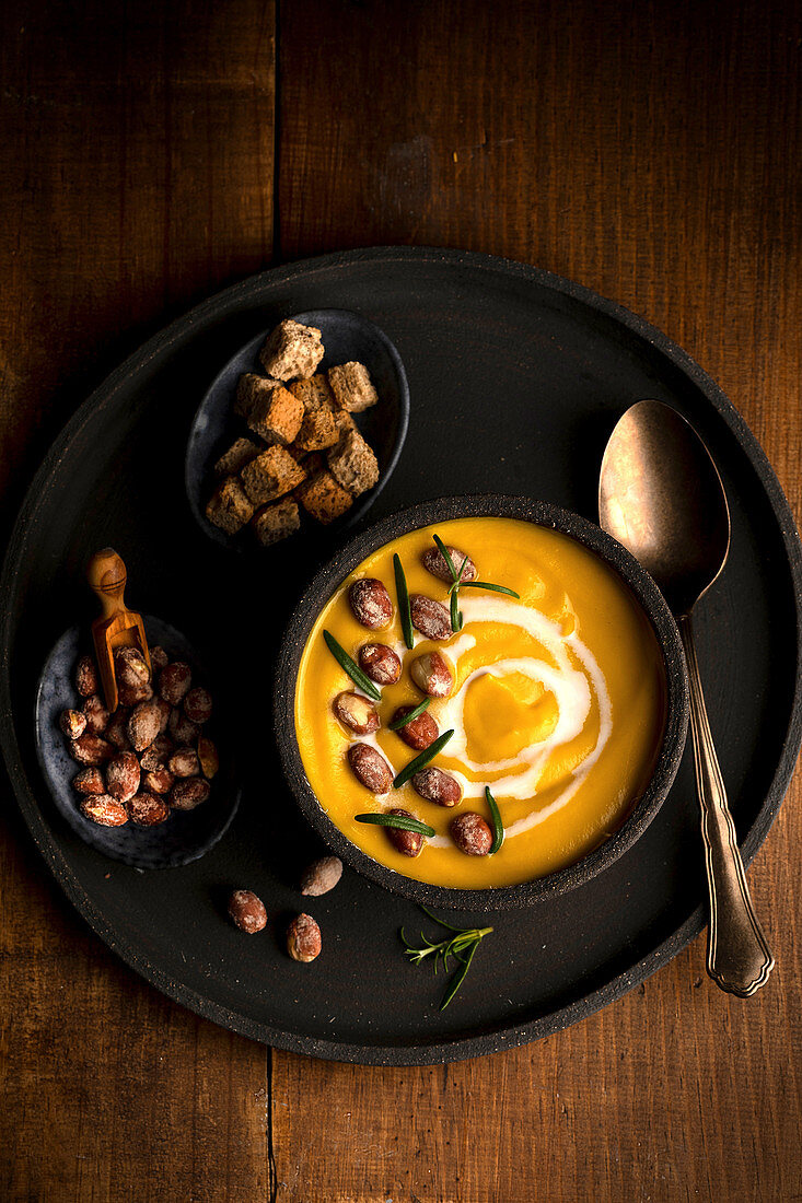 Pumpkin soup in bowl served on tray with crispy bread croutons and nuts