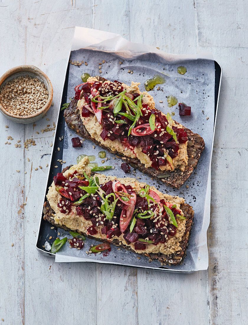 Bread topped with hummus, beetroot tartare and sesame seeds