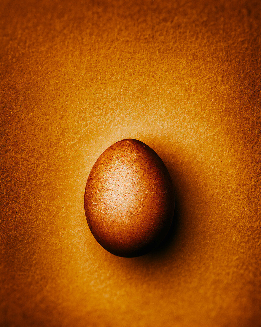 Golden Easter egg on a gold-colored background