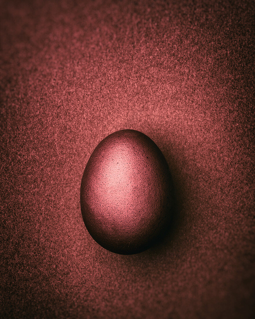 Rust-brown Easter egg on a rust-brown background