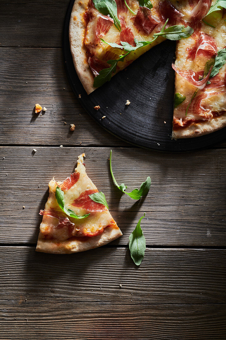 Pizza decorated with fresh basil and arugula leaves