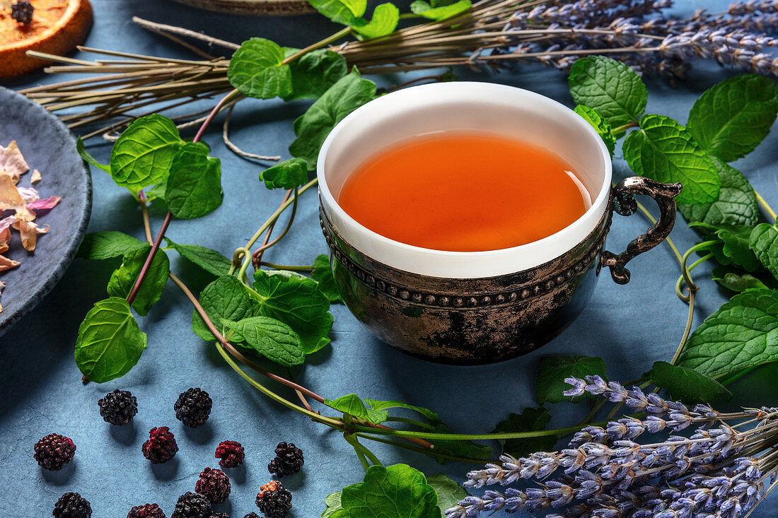Cup of herbal tea and an assortment of ingredients, herbs, fruits and flowers