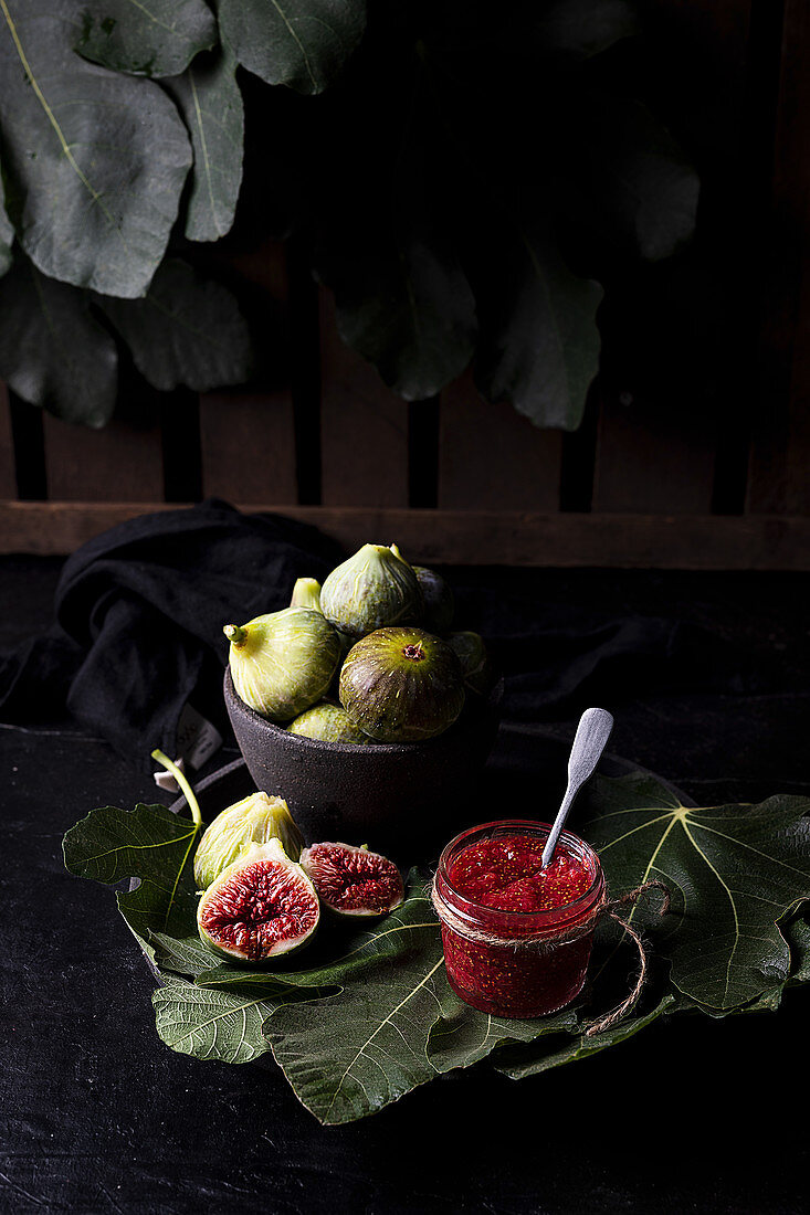 Homemade jam in glass jar made of ripe fresh figs placed on table