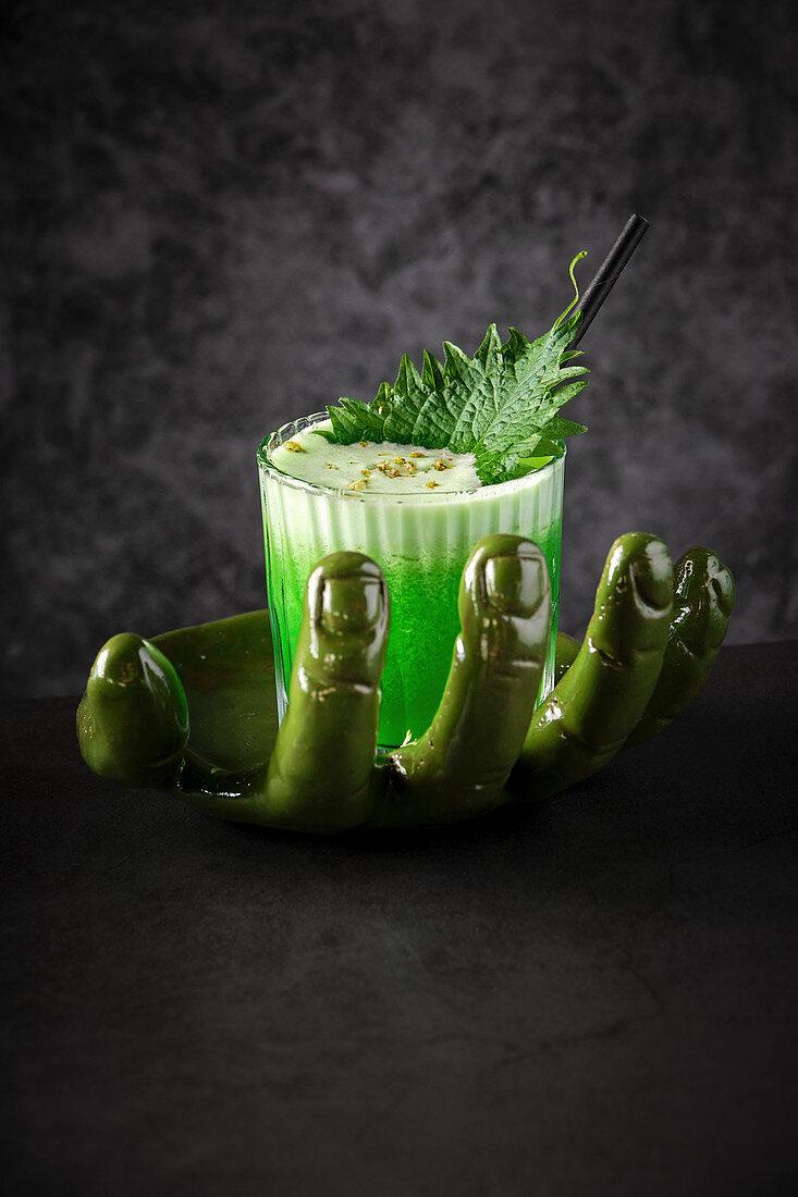 Grüner Smoothie mit Schaum und Blatt, serviert auf handgeformter Schale