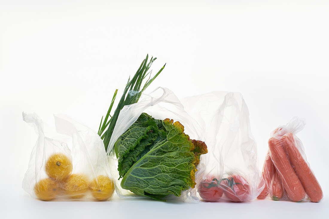 Still life with food in plastic bags on white background