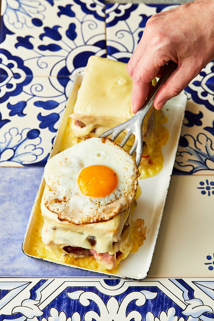 A Portuguese Francesinha (toasted sandwich with meat, cheese and a fried egg) being made