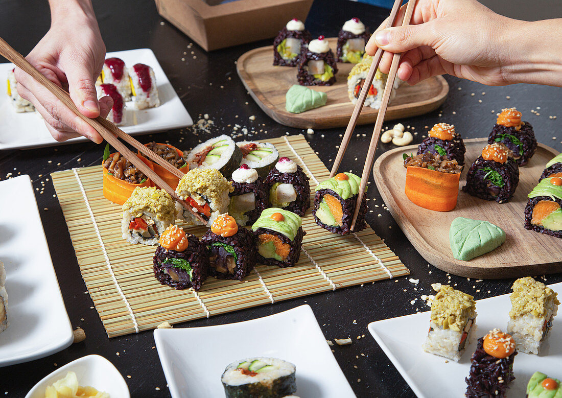 Hands with chopsticks taking assorted veggie sushi