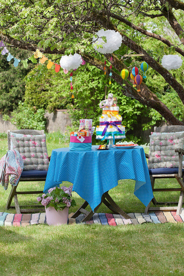 Colorful table with diaper cake and garlands for a baby shower party