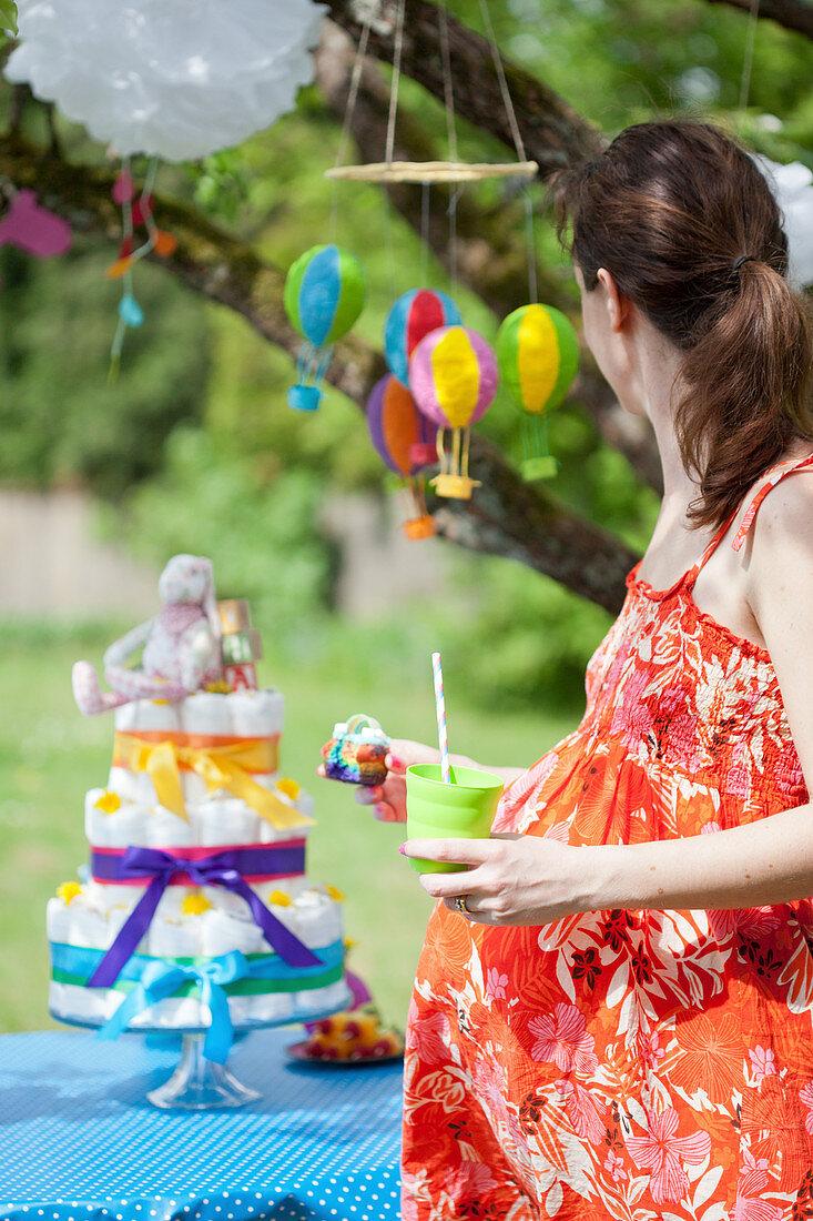 Schwangere Frau vor einer Windeltorte auf einer Baby Shower Party
