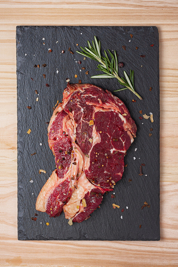 Raw rib eye beef steak with rosemary sprig and spices