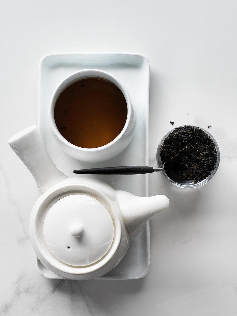 Black tea leaves with tea pot