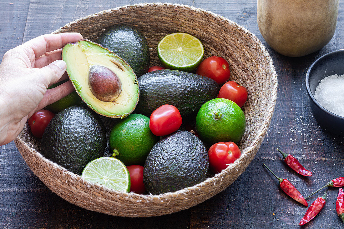 Person taking half of avocado from bowl with ingredients for Mexican guacamole