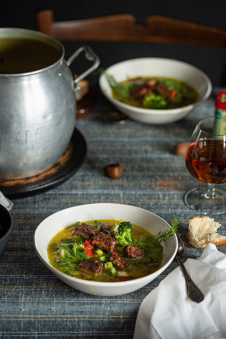 Hot soup with green herbs and meat