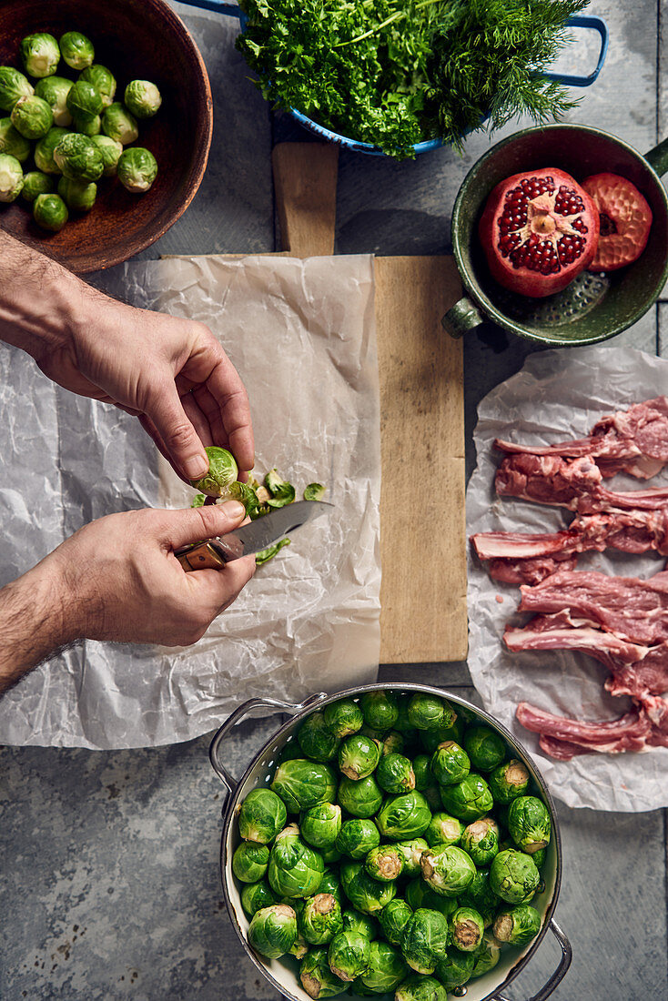 Brussels sprouts being trimmed next to raw lamb chops and herbs