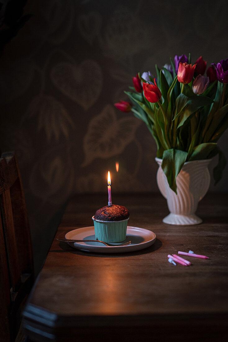 Birthday chocolate cupcake with burning candle