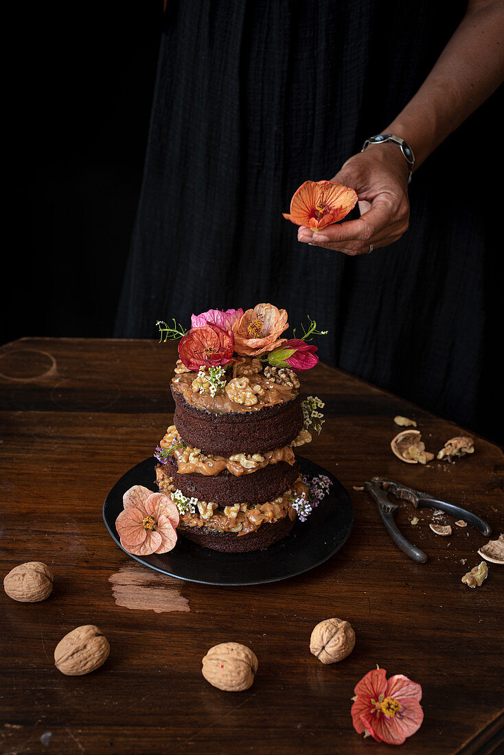 Chocolate naked cake with walnuts and edible flowers
