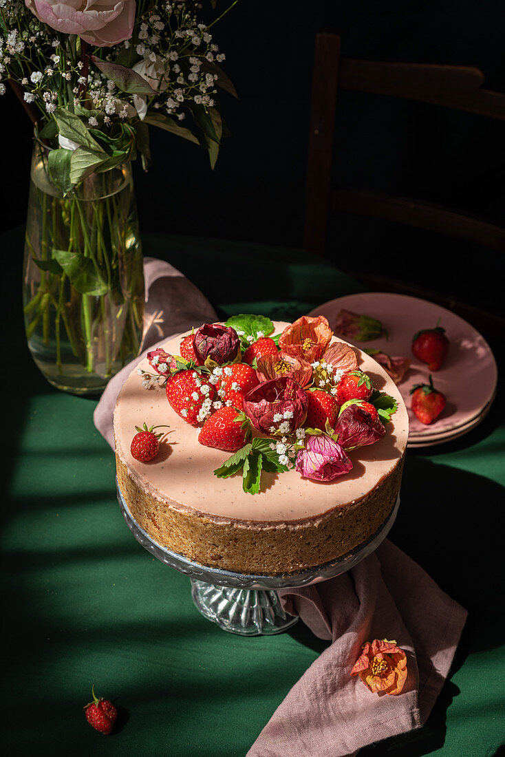 Strawberry cheesecake decorated with fresh berries and flowers