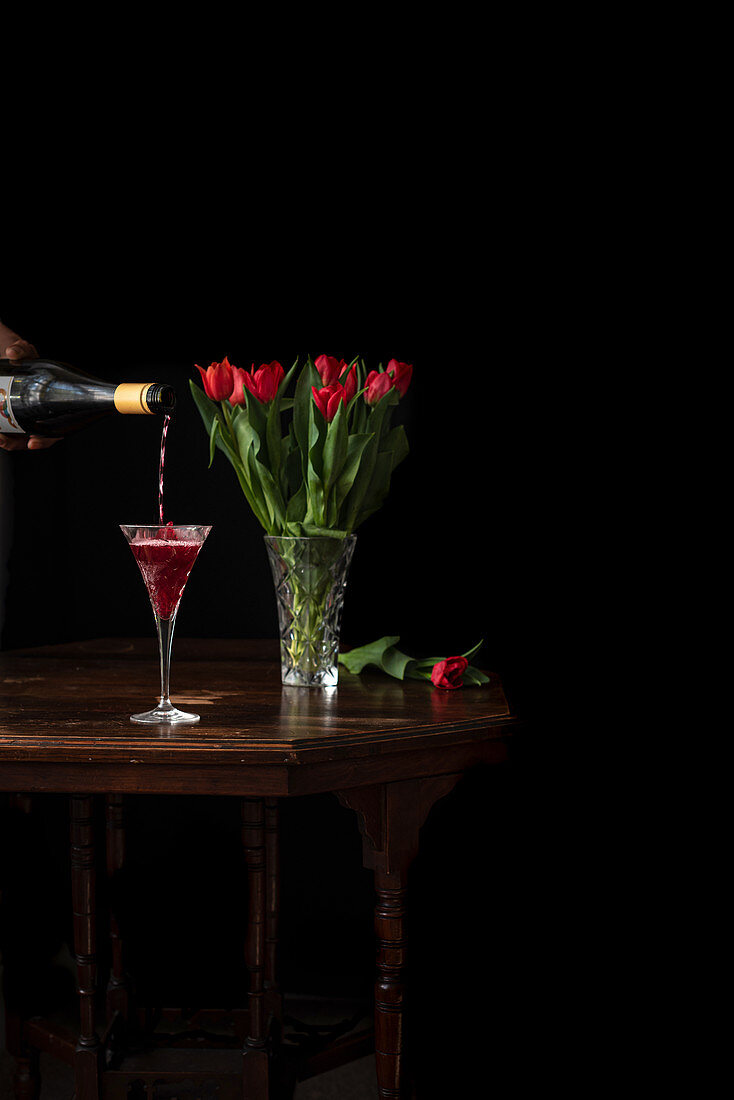 Pouring sparkling wine in glass, bouquet of red tulips