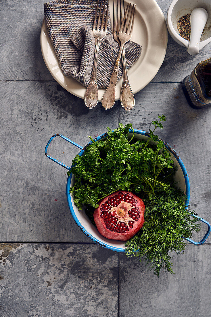 Pomegranate, parsley and dill in an enamel colander
