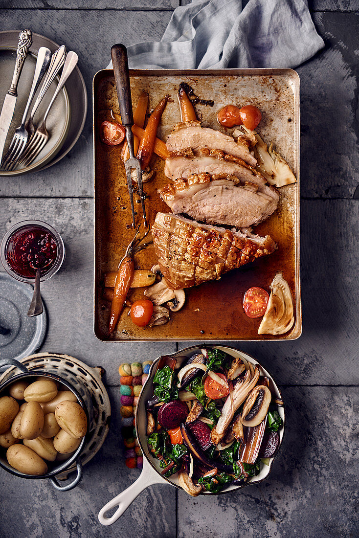 Crispy roast pork with oven-roasted vegetables and new potatoes