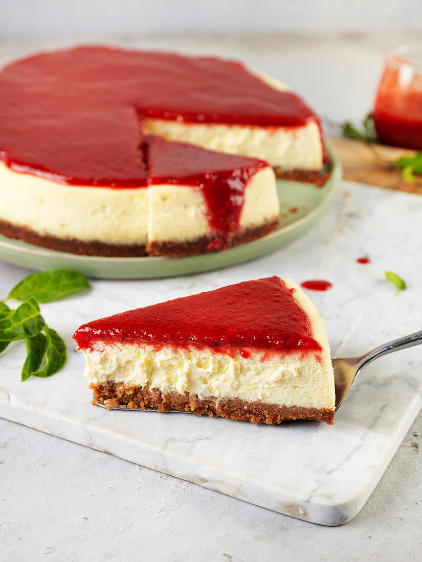 New York cheesecake with strawberry sauce, sliced