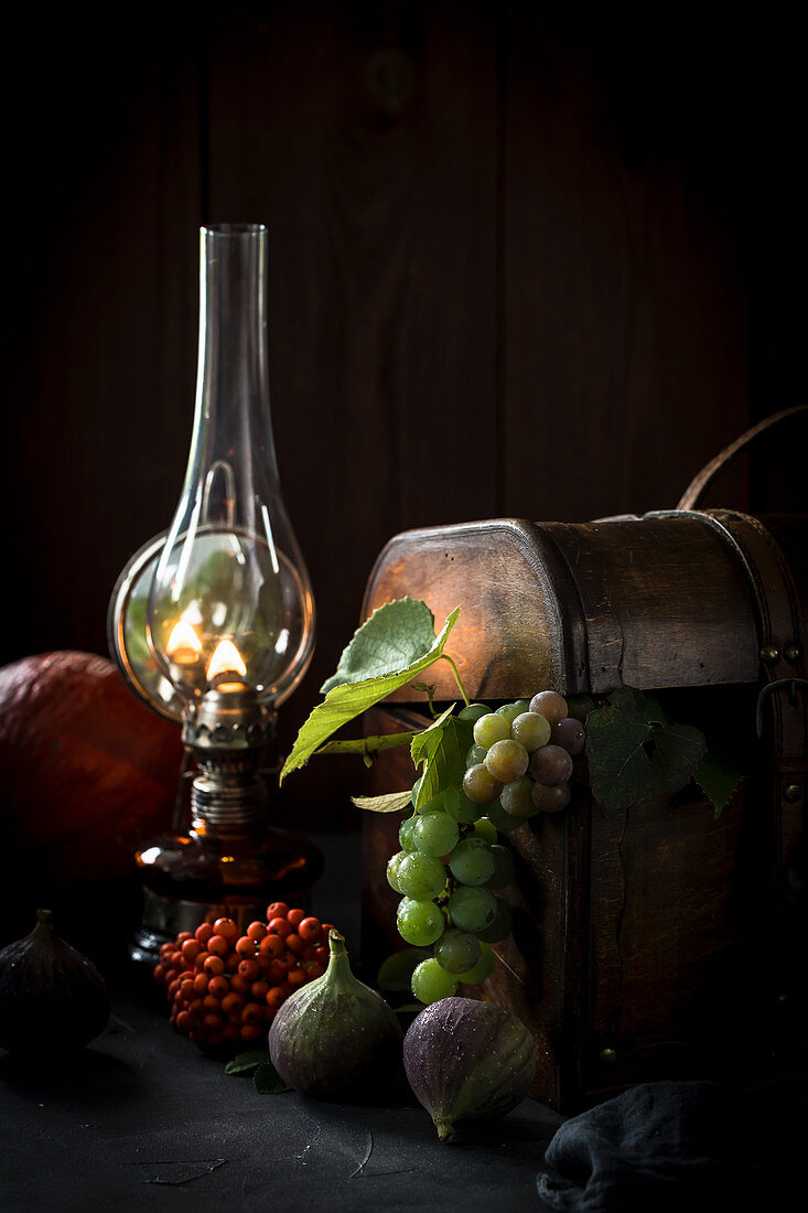 Autumn still life with fruits, a wooden box and a kerosene lamp