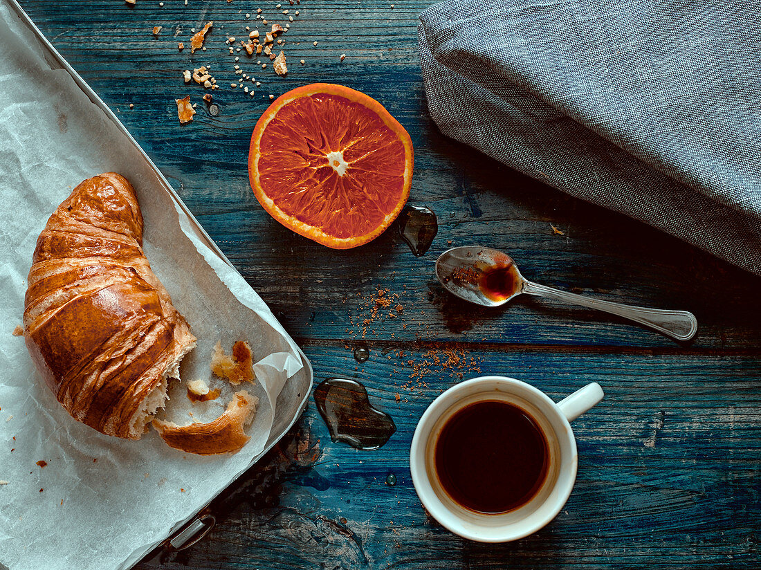 Italian breakfast at home with a croissant, espresso and orange half