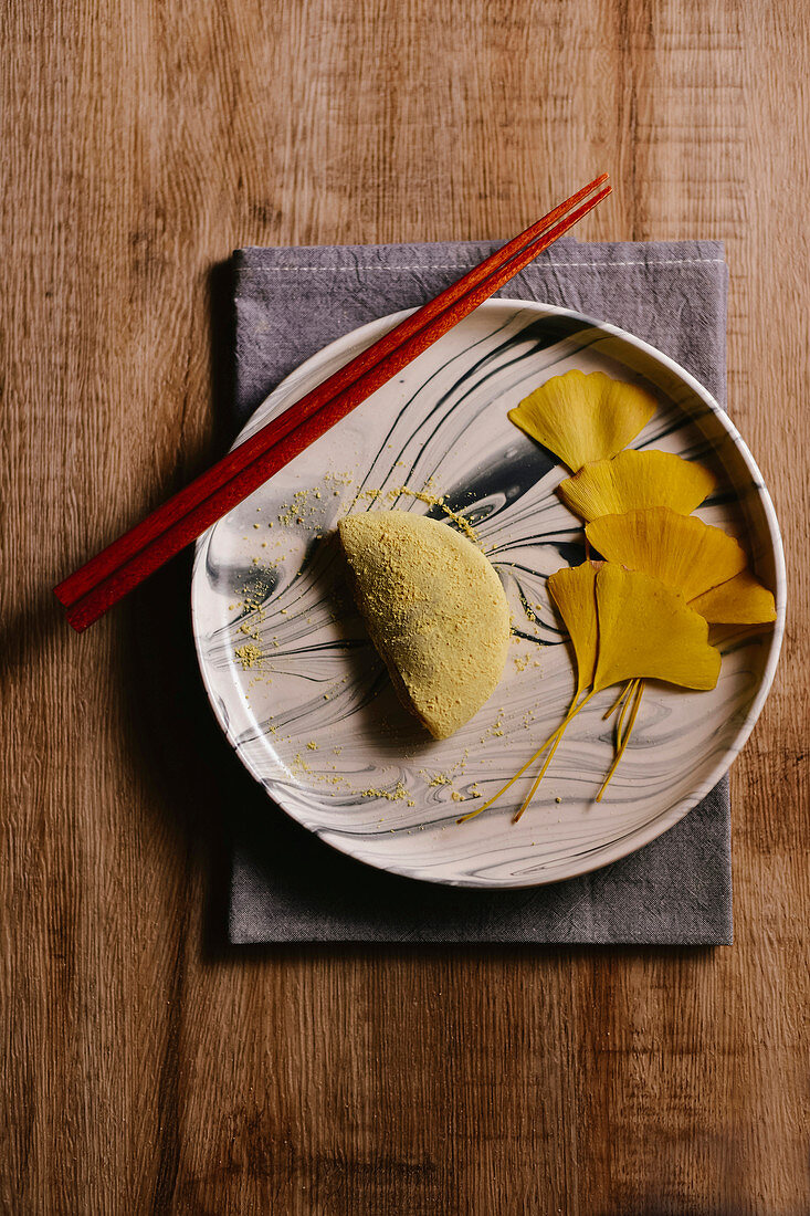 Sticky rice cake on a plate decorated with gingko leaves (Asia)