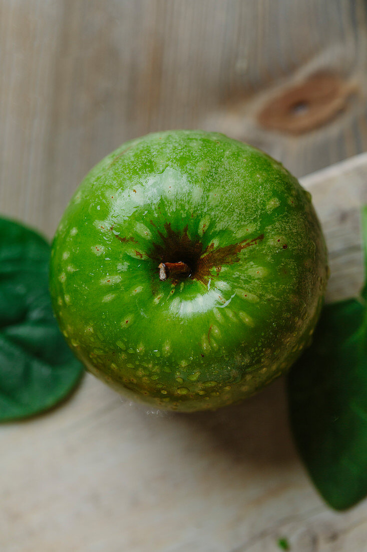 Green apple on wooden surface