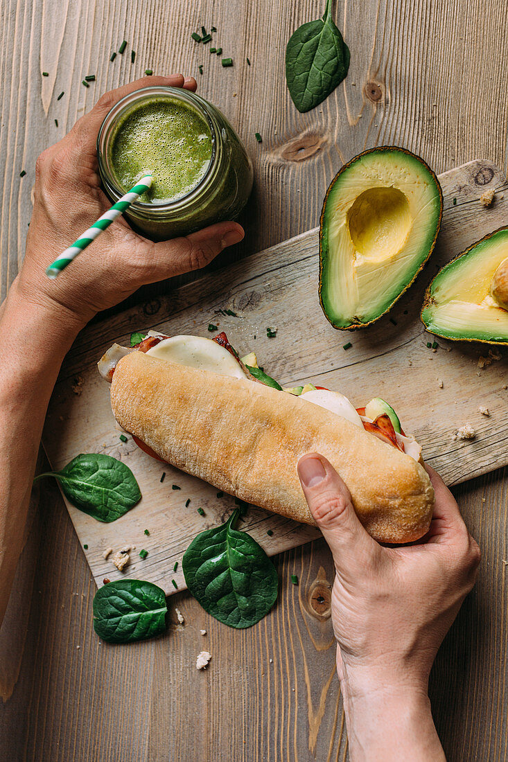 Hand holding a panini with turkey and avocado and detox veggie smoothie