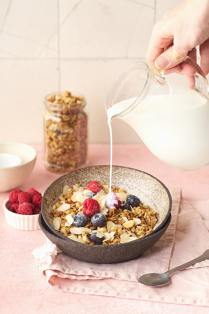 Pouring milk to granola with nuts, oats and berries