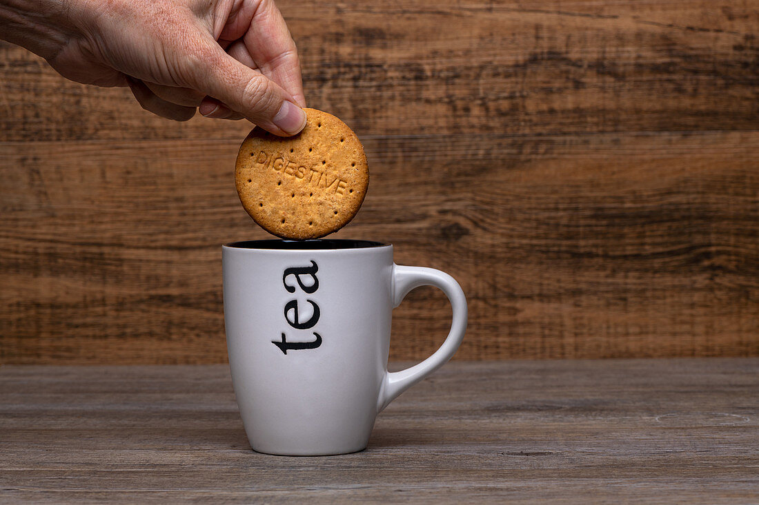 Person holding cookie over white mug with hot coffee