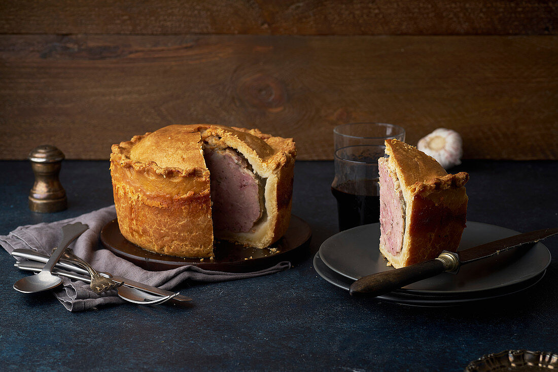 Traditional British raised pork pie with bacon and herbs