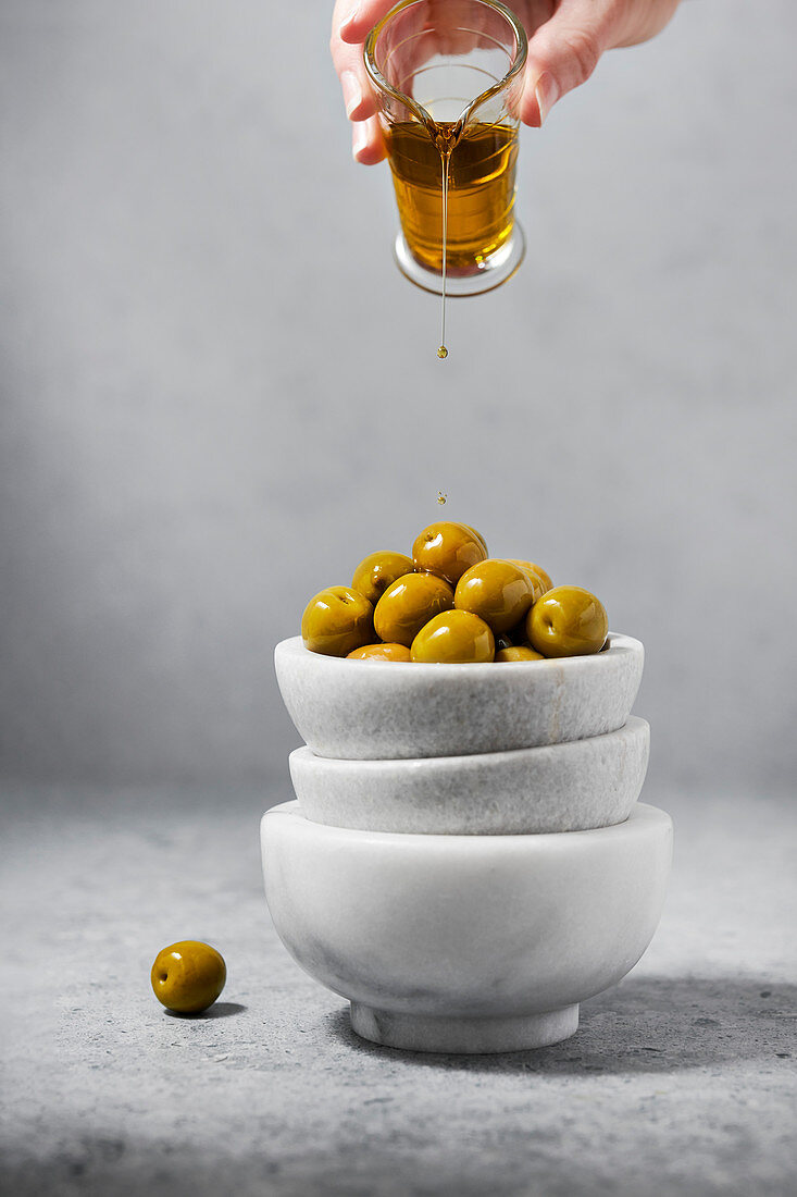 Marble bowls filled with green olives being drizzled with olive oil by a woman's hand