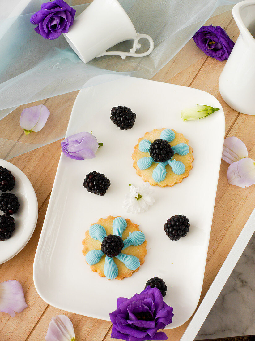 Cheese decorated with blue buttercream and blackberries