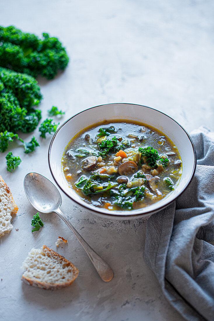 Mushroom and pearl barley broth with kale leaves