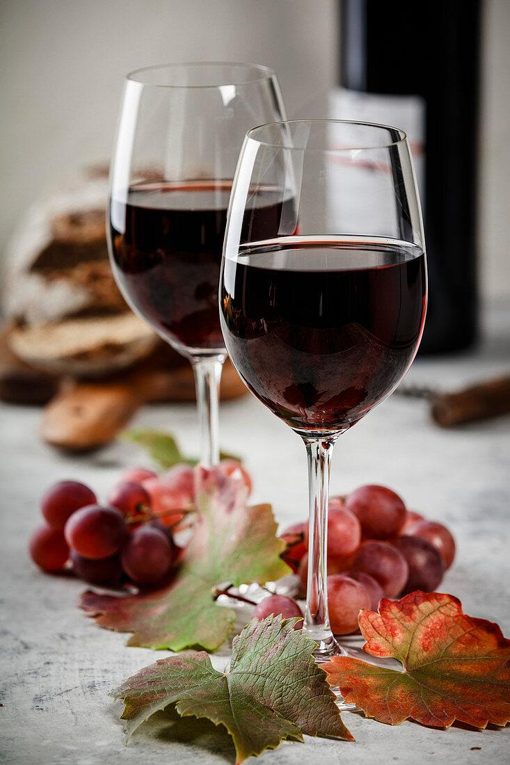 Zwei Gläser Rotwein, Trauben und Weinblätter