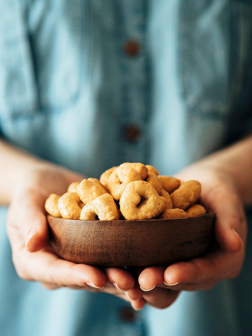 Traditional italian snack tarallini in wooden bowl in female hands