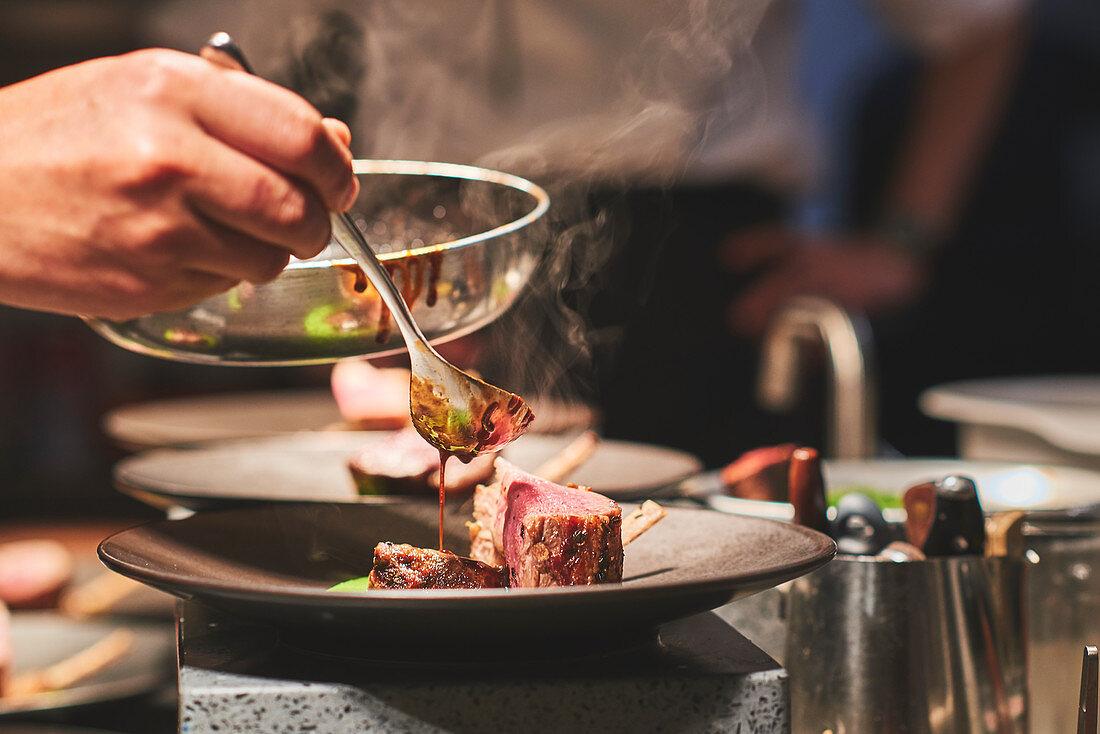 Schweinefilet mit Sauce beträufeln in französischem Restaurant