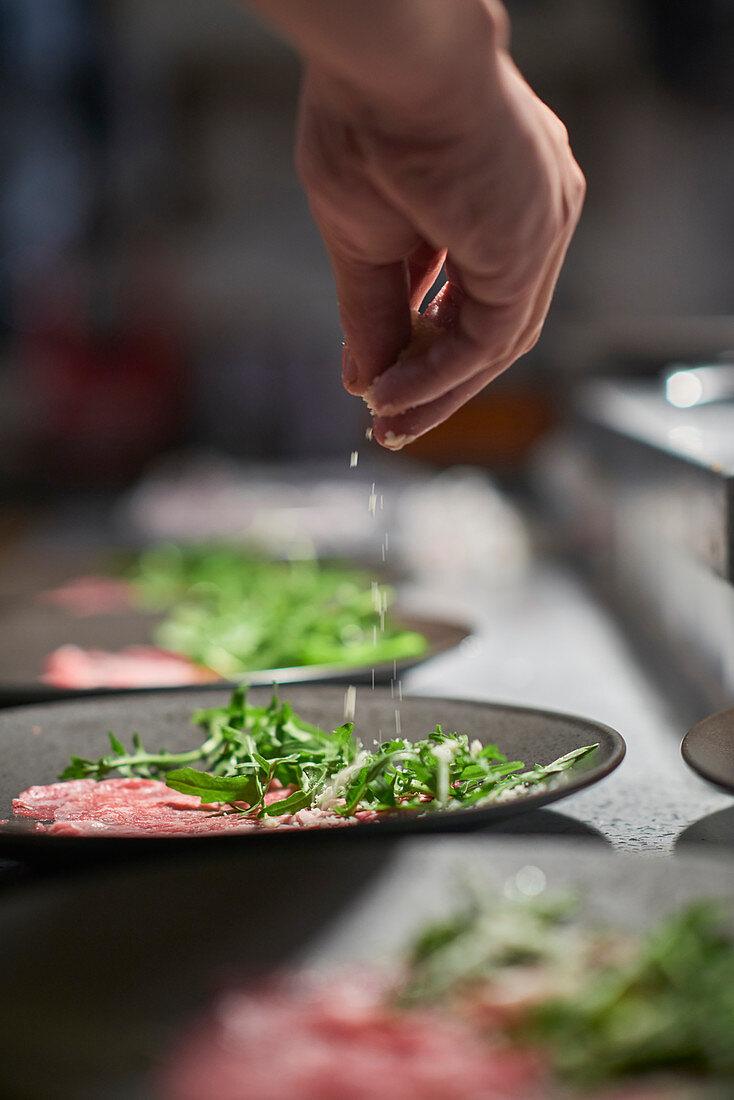 Koch würzt Salat in französischem Restaurant