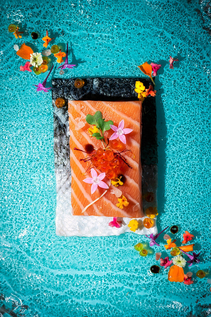 Raw salmon fillet decorated with flowers and caviar