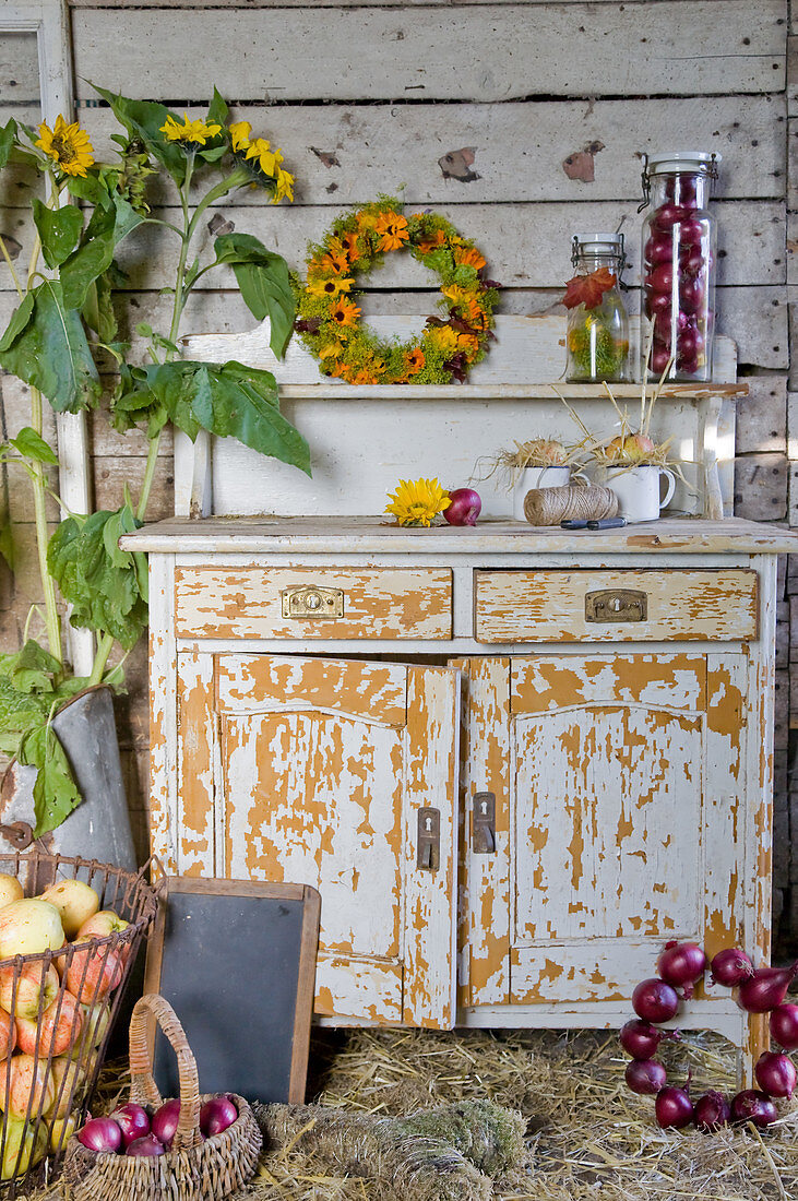 A harvest still life with apples, red onions, an autumn wreath and sunflowers near an old kitchen cupboard