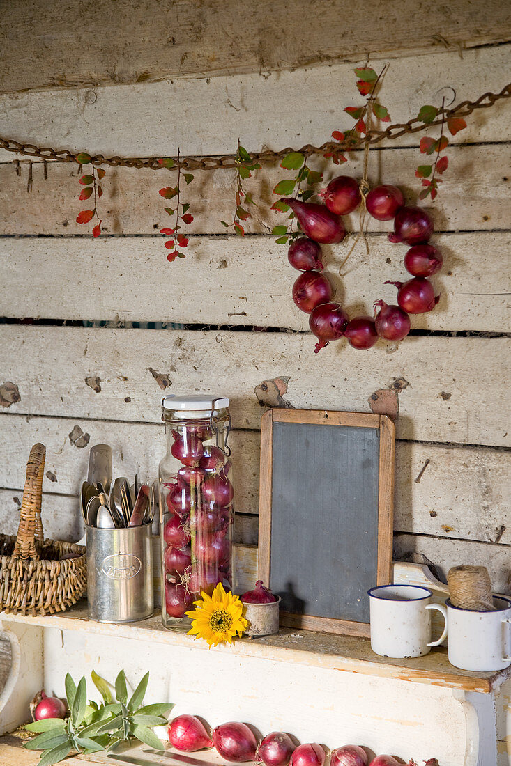 Autumn arrangement with red onions, a slate board, cutlery and cups