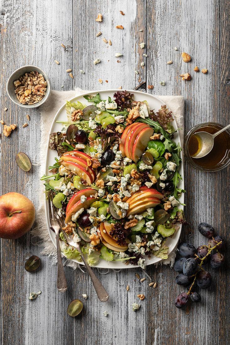 Apple salad with grapes, gorgonzola, celery sticks, walnuts and mustard dressing
