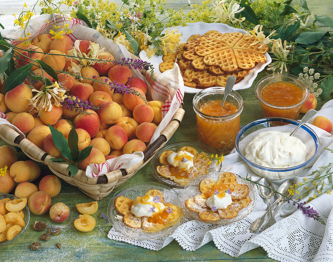 Still life with apricots, apricot jam, waffles, whipped cream
